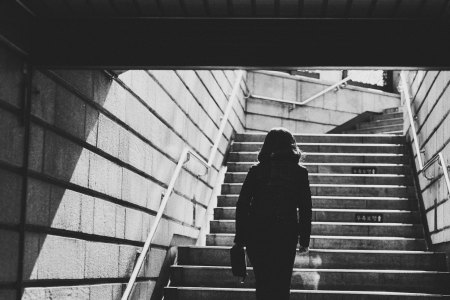 black and white image of woman walking up stairs