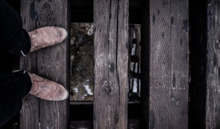 Boots on slatted wooden bridge